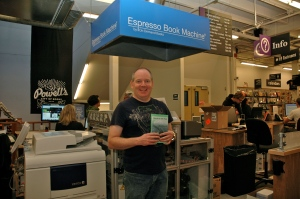 Michael Gettel-Gilmartin holds a copy of Brave on the Page at the Powell's Espresso Book Machine.