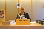 Yuvi Zalkow, author of A Brilliant Novel in the Works, which is about a novelist named Yuvi, holds a copy of his book and poses by his name and a picture of himself. So many Yuvis in one photograph!