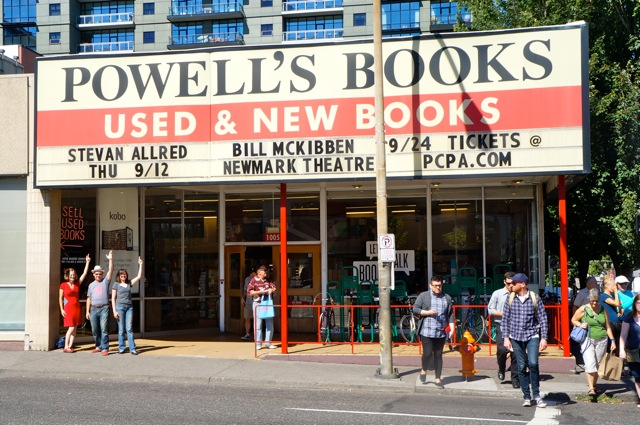 Laura Stanfill, Stevan Allred, and Gigi Little stand under the Powell's marquee advertising the book launch.